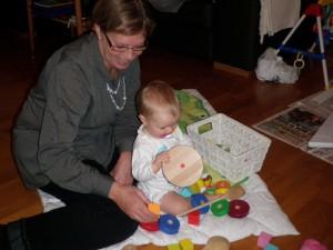 En sjuk tjej bygger klossar med farmor